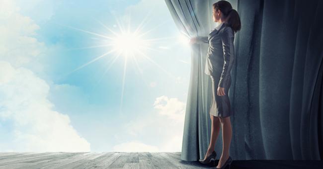 Jeune femme habillée en tailleur qui ouvre ses rideaux pour faire apparaître le soleil