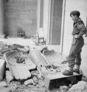 Sergeant_R_S_Baker_of_the_Army_Film__Photographic_Unit_AFPU_looks_at_a_fallen_Nazi_eagle_and_swastika_amidst_the_ruins_of_Hitlers_Reich_Chancellery_in_Berlin_3_July_1945._BU8560