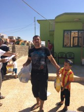 A Dad and his boy receive food and supplies for the family.