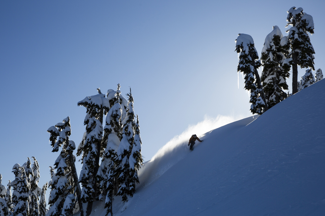 Snowboarding. 18-19 JHSM. Rider Mike Basich chased by a illuminated rooster tail. Photo: Ben Gavelda.