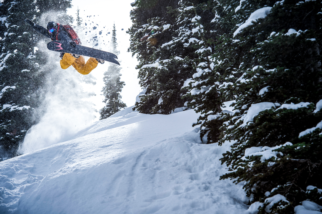 Snowboarding. 18-19 JHSM. Professional snowboarder Rob Kingwill throws a method air through the trees. Photo: Chad Chomlack.