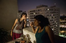 Two women uncover their heads, light up a cigarette, and relax on their balcony