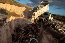 A truck dumps rubble into a pit full of the dead in Titanyen after a devastating earthquake struck Haiti, Jan. 16, 2010. Chris Hondros/Getty Images