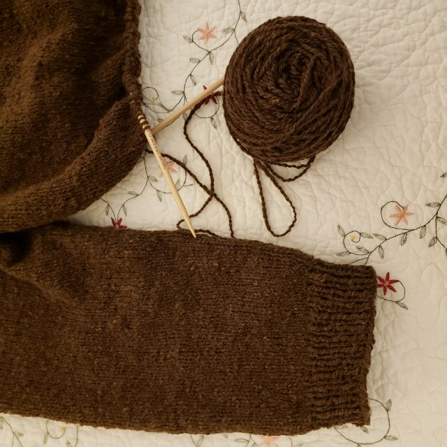 A completed sleeve is shown across the bottom of the picture. Above the sleeve is the partially knit body of the sweater, still on the needles, with a ball of handspun wool next to it.