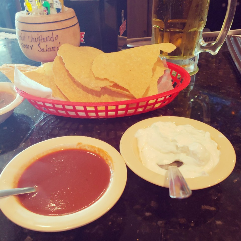 bowls of enchilada sauce and sour cream with a large beer and basket of large chips in background