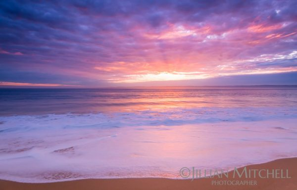 Gorgeous pink skies reflect across the water on Phillip Island, Melbourne, Australia.