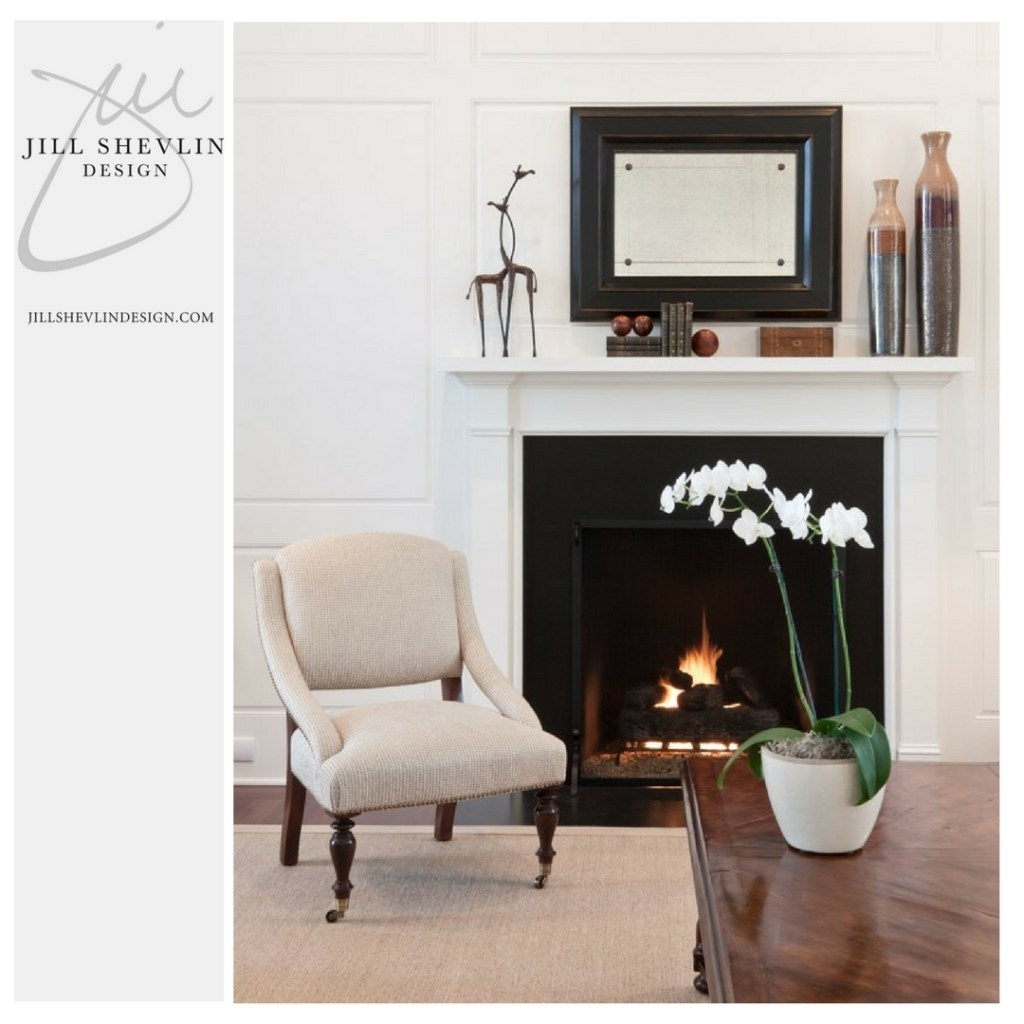 Simple White Millwork Details surround a Classic Fireplace with Black Granite Surround