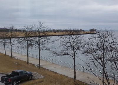 The truck at the end of the parking lot. From inside Milwaukee Art Museum. (that is Lake Michigan)