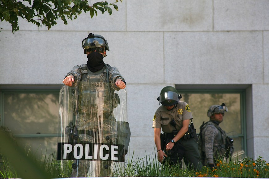 A police officer, sheriff, and National Guard service-member guard the Hall of Justice in downtown Los Angeles