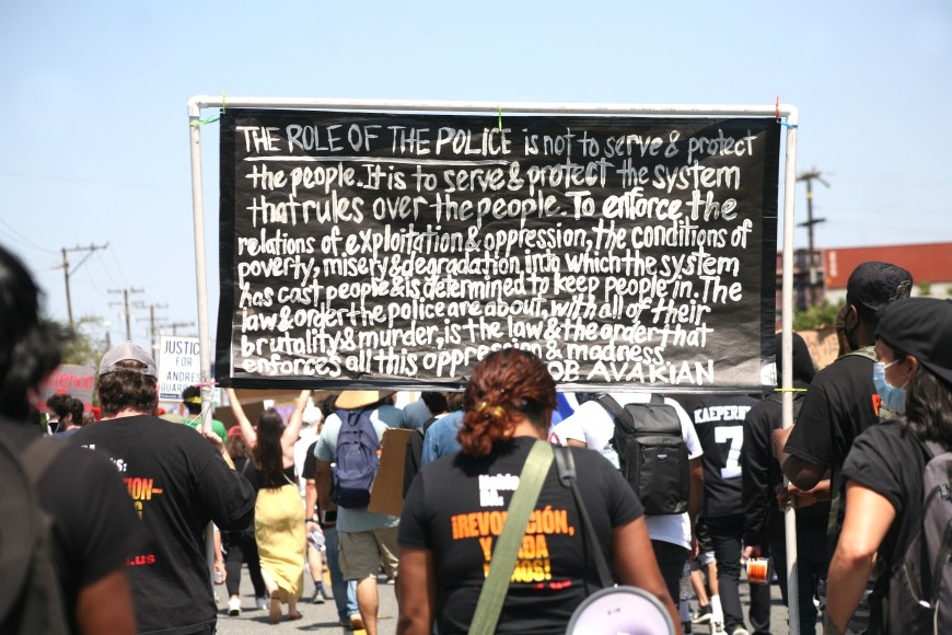 Marchers hold a sign up with a statement from Bob Avakian regarding the role of police in America