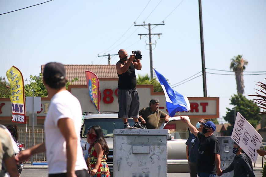 Marchers hold signs up, as well as the Salvadoran flag, along Compton boulevard en route to the Compton sheriff department