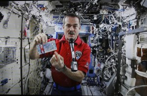 Canadian Space Agency astronaut Hadfield, the commander of the ISS, is seen on a screen holding the new Canadian five dollar bill, while on a space mission, as he takes part in a video conference in Ottawa