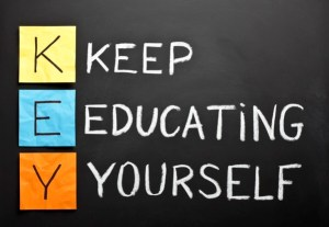 KEY acronym - KEEP EDUCATING YOURSELF. Educational concept with different color sticky notes and white chalk handwriting on a blackboard.
