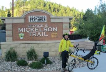 Jim-Schmid-with-Bacchetta-Giro-recumbent-at-Mickelson-Trail-sign-Deadwood-SD-5-28-2016