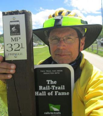Jim-Schmid-next-to-Rail-Trail-Hall-of-Fame-sign-on-Mickelson-Trail-SD-5-31-2016