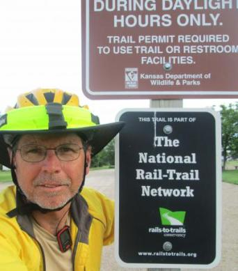 Jim-Schmid-next-to-Rail-Trail-Network-sign-on-Prairie-Spirit-Trail-Ottawa-to-Iola-KS-6-3-2016