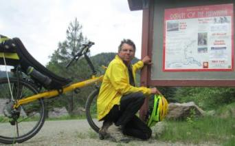 Jim-Schmid-with-Bacchetta-Giro-recumbent-next-to-sign-on-Route-of-the-Hiawatha-ID-5-26-2016