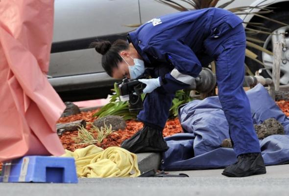 เจ้าหน้าที่หญิงหนึ่งในทีมนิติวิทยาศาสตร์กำลังตรวจพื้นที่บริเวณที่เกิดเหตุ ภาพจาก Daily News (ออสเตรเลีย)