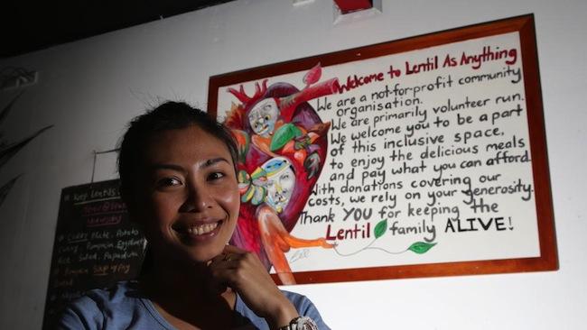 คุณ Piyarach Kiatsiri กับป้ายที่แสดงตัวว่าร้าน Lentil as Anything เป็นชุมชนหรือองค์กรที่ไม่หวังผลกำไร : ภาพชั่วคราวจาก theheodistlife.wordpress.com
