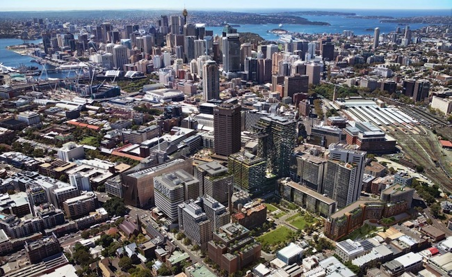กลุ่มอาคาร Central Park ตึกสูง ๆ ด้านหลังสนามหญ้าเขียว ๆ ตรงข้ามถนนเห็นถึงสีน้ำตาลเข้มของม. UTS : ภาพจาก Centralparksydney.com