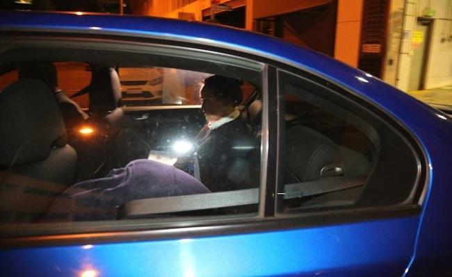 ภาพผู้ต้องหาหญิงวัย 25 ปีสวมเสื้อสีม่วงอ่อนมีฮูดคลุมศีรษะนั่งก้มหน้าอยู่เบาะหลังรถ ขณะถูกนำตัวออกจากวอทช์เฮาส์ในคืนวันที่ 28 ก.ย.