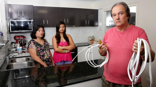 นาย Nev Roser พร้อม Marlynda ภรรยาและ Vanessa บุตรสาวพบว่าบ้านของพวกเขาที่ย่าน Elimbah ในนครบริสเบนเดินสายไฟนำเข้าจากบริษัท Infinity Cable ที่อาจเป็นสาเหตุเกิดไฟไหม้บ้านได้ทุกเวลา : ภาพจากนสพ. Courier Mail