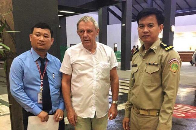 นาย Guido James Eglitis ถ่ายภาพกับเจ้าหน้าที่กัมพูชาขณะได้รับการปล่อยตัวเมือสัปดาห์ที่ผ่านมา : ภาพชั่วคราวจากนสพ. Phnom Penh Post