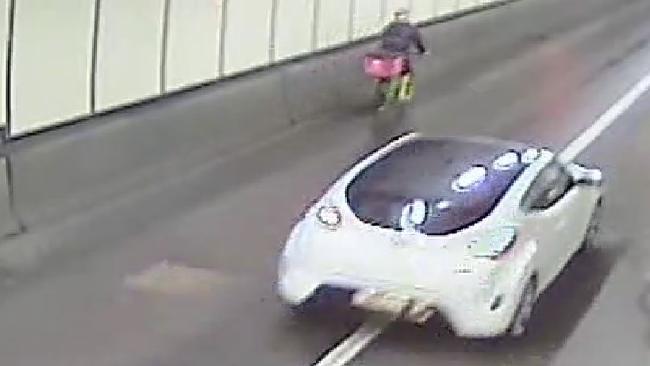 พนักงานส่งอาหารรายหนึ่งกำลังปั่นจักรยานโดยใช้ทางลอดอุโมงค์ ทำให้รถสีขาวที่ตามมาต้องแซงขวา : ภาพจากกล้อง CCTV
