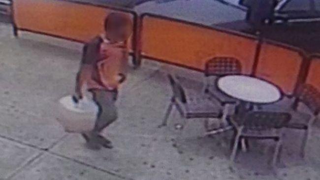 กล้อง CCTV แสดงให้เห็นชายผู้ขอลี้ภัยกำลังถือถังสีขาวบรรจุน้ำมันเบนซินเดินไปยังธนาคาร : ภาพจากนสพ. The Age