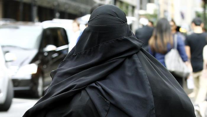 นาง Moutia Elzahed ขณะมาศาลในวันที่ 7 ธันวาคม ด้วยชุดบุรกาปกปิดทุกส่วนของร่างกายแม้แต่ดวงตา : ภาพจากนสพ. Telegraph