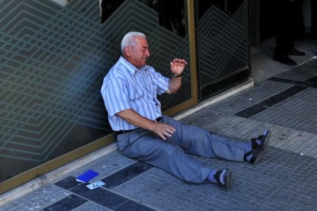 ผู้รับเงินสวัสดิการผู้สูงอายุในประเทศกรีซนั่งระทมทุกข์อยู่ที่ทางเข้าธนาคารกลางกรีซสาขาหนึ่ง ในช่วงที่รัฐบาลถังแตกจนกระทบต่อผู้รับเงินสวัสดิการ : ภาพจากสำนักข่าว AFP