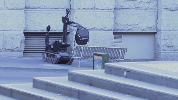 หุ่นยนต์กู้ระเบิดทำงานด้วยการนำกระเป๋าต้องสงสัยไปวางไว้ในจุดปลอยภัยที่สุด : ภาพชั่วคราวจากนสพ. The Age