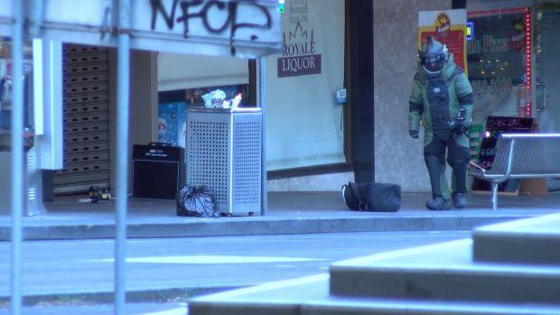 เจ้าหน้าที่กู้ระเบิดขณะเข้าตรวจสอบกระเป๋าต้องสงสัย : ภาพชั่วคราวจากนสพ. The Age