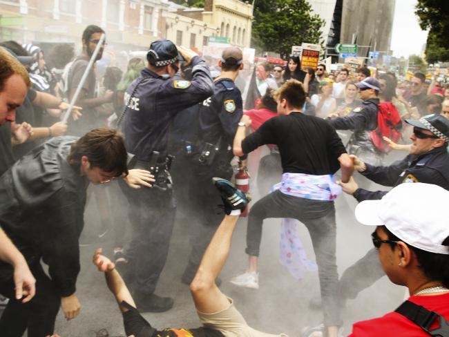 การปะทะกันระหว่างกลุ่มผู้ประท้วงหัวรุนแรงกับตำรวจหลังผู้ประท้วงคนหนึ่งเริ่มจุดเผาธงชาติ ส่วนควันที่เห็นมาจากเครื่องดับเพลิงที่ตำรวจพ่นดับไฟ : ภาพชั่วคราวจากนสพ. Herald Sun