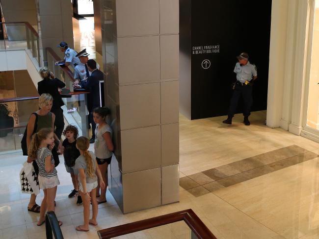 ตำรวจยืนเฝ้าอยู่หน้าทางเข้าไปประตูบันไดหนีไฟของศูนย์การค้า Westfield ในย่าน Bondi Junction ที่พบศพนาย Bernard Gore : ภาพชั่วคราวจากนสพ. The Telegraph