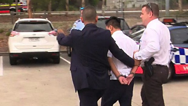 ตำรวจใส่กุญแจมือนำตัวนักเรียนชาวเอเชียวัย 16 ปีผู้ต้องหาไปขึ้นรถ : ภาพชั่วคราวจากนสพ. The SMH