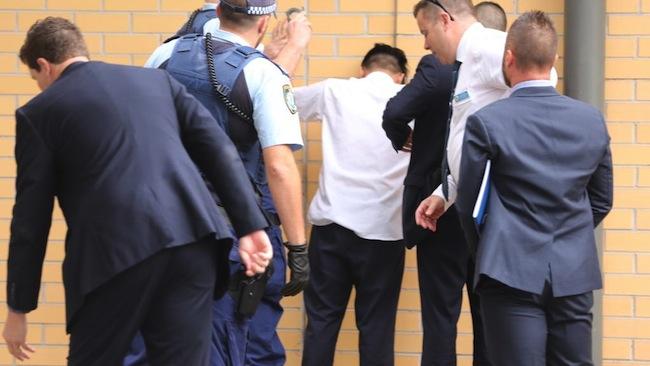 ตำรวจขณะจับนักเรียนชาวเอเชียวัย 16 ปีนำมายืนหันหน้าเข้าหาผนังอาคารซูเปอร์มาร์เก็ตเพื่อค้นอาวุธตัวก่อนใส่กุญแจมือ : ภาพชั่วคราวจากนสพ. The Telegraph