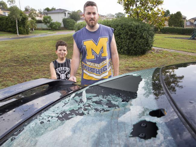 เจ้าหนู Benji Little ยืนยิ้มส่วนพ่อ Ben Little ยืนหน้าบอกบุญไม่รับเมื่อเห็นกระจกรถของเขาถูกลูกเห็บตกลงมากระแทกแตกกระจายที่ทางเข้าหน้าบ้านย่าน Rouse Hill : ภาพจากนสพ. Sunday Telegraph