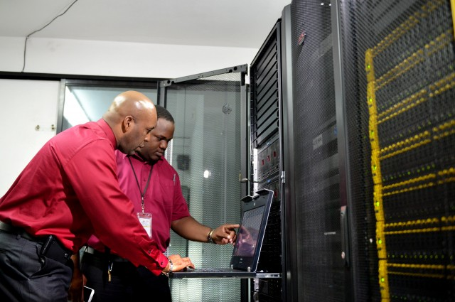 Chief Information Officer of the Jamaica Customs Agency (JCA) Andre Williams (left) and Acting Operations Manager, JCA, Owen Gayle, observe data on a laptop in the JCA's server room. The JCA is implementing the Automated System for Customs Data (ASYCUDA), a web-based system designed to transform the agency to a paperless operation through the use of electronic documents.