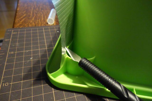 水耕栽培の容器に遮光テープを貼っている様子。カッターで切り込みを入れて容器にフィットさせている様子。