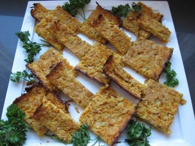 Potato Kugel, cooked thin and crispy, sliced and served on a large white ceramic tray, garnished with parsley
