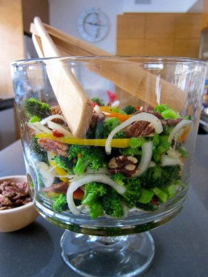 broccoli sweet onion pecan salad, served in a tall glass pedestal bowl from Pampered Chef with wooden tongs, with a bowl of extra pecans on the side and a view of Jittery Cook's kitchen in the background