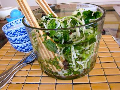 Healthy Salad, coleslaw, in a big tall glass salad bowl with wooden spoon servers, small blue and white bowls from Thailand, on a bamboo placemat with forks