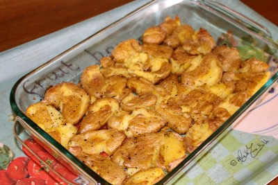 Roasted Smashed New Potatoes in a large glass, rectangular dish, on a colourful turquoise tray