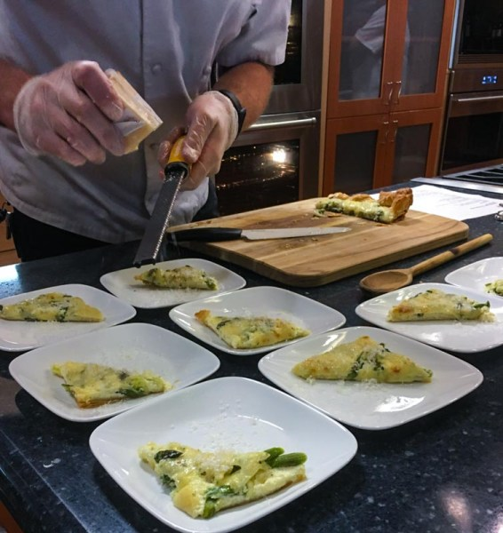 asparagus gruyere tart slices on many plates being garnished with grated gruyere