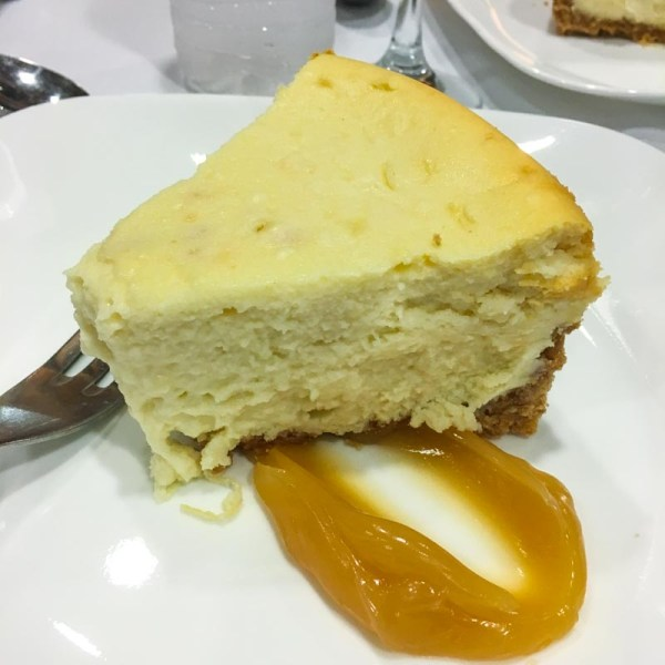 cheescake on a plate garnished with lemon curd