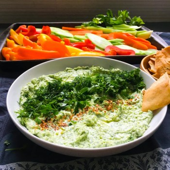 Feta Dill Dip in a white shallow bowl, stoneware platter of sliced vegetables, small wooden bowl of Stacey's baked pita crackers