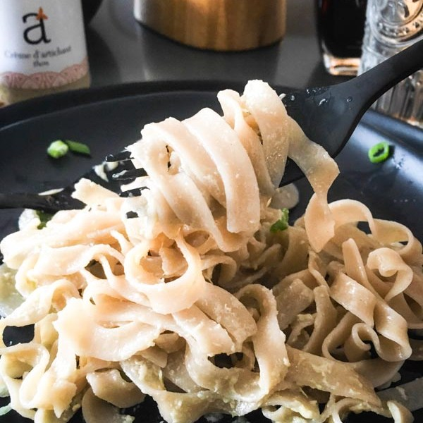 Close up of artichoke tuna pasta on a black plate with a jar of the artichoke tuna sauce in the background.