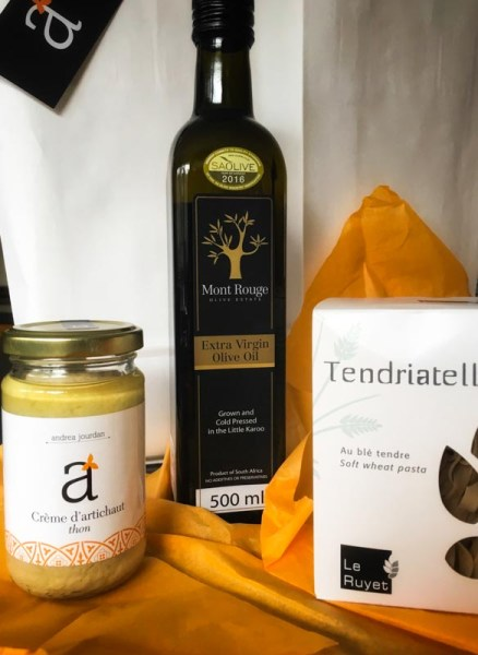 Olive oil from South America, a jar of artichoke tuna sauce and Tendriatell pasta in a box on orange tissue paper with white gift bags in the background.