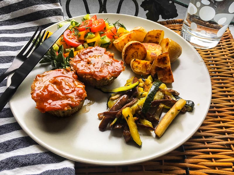 Lamb Meatloaf with Sweet and Spicy Topping cooked in muffin cups. Served on a white plate with grilled zucchini and eggplant, roasted sweet potatoes and salad.